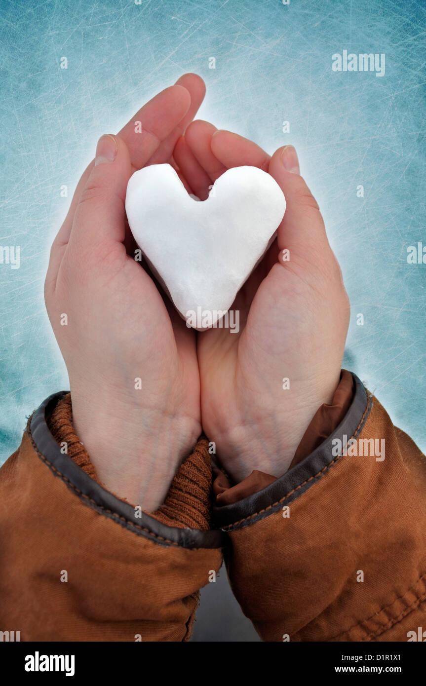 Giovane donna di contenimento a forma di cuore snowball Immagini Stock