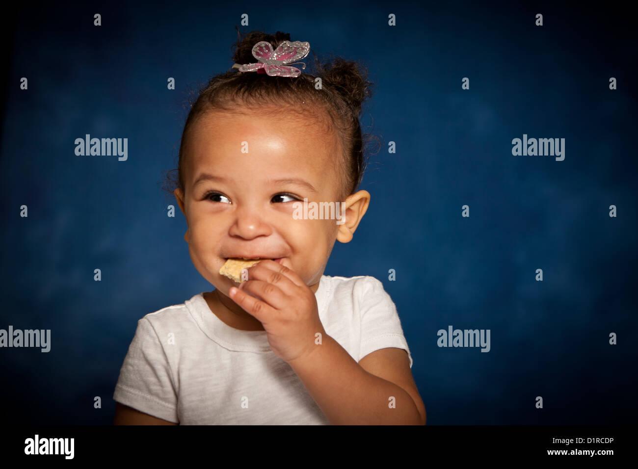 Carino studio ritratto di una razza mista toddler girl mangiando un biscotto con una cheeky sorriso sul suo viso Immagini Stock