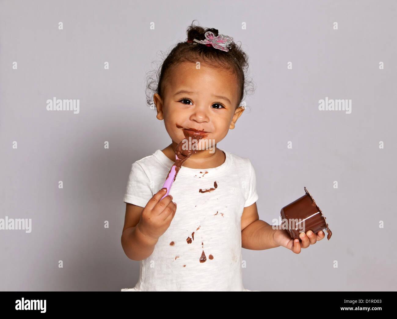 Carino bambina, bimbo, facendo un pasticcio di mangiare una cioccolata deserto. Immagini Stock