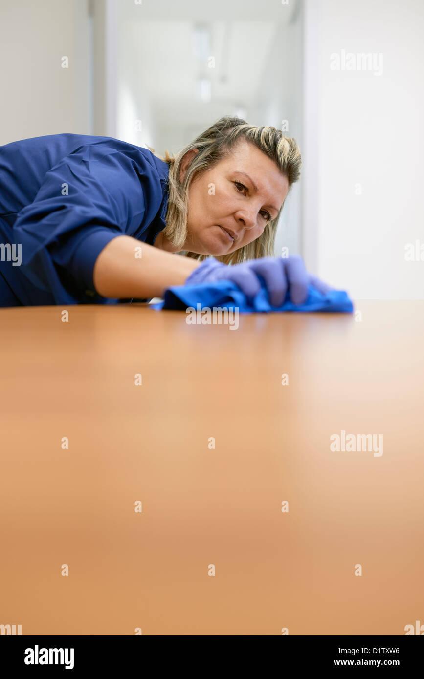 Donna al lavoro professionale di pulizia pulizia scrivania in ufficio. Spazio di copia Immagini Stock