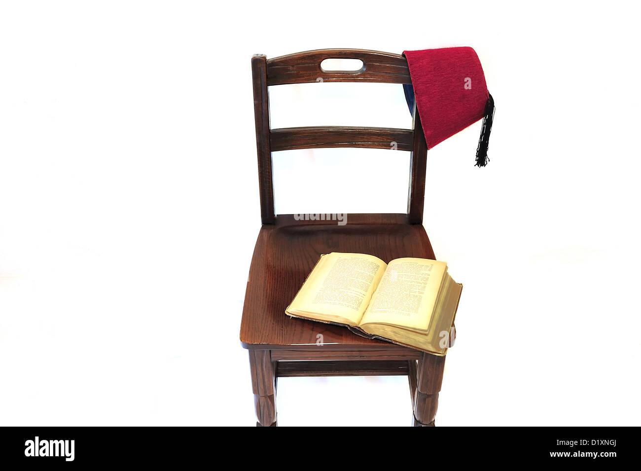 Un vecchio libro aperto lasciato aperto su una vecchia sedia. Un centro storico orientale coperchio della testa Immagini Stock