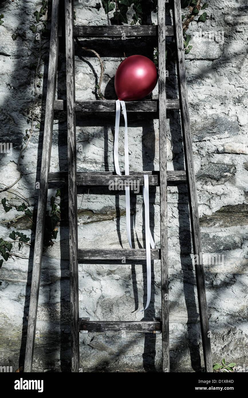 Un palloncino rosso su una vecchia scala di legno Immagini Stock