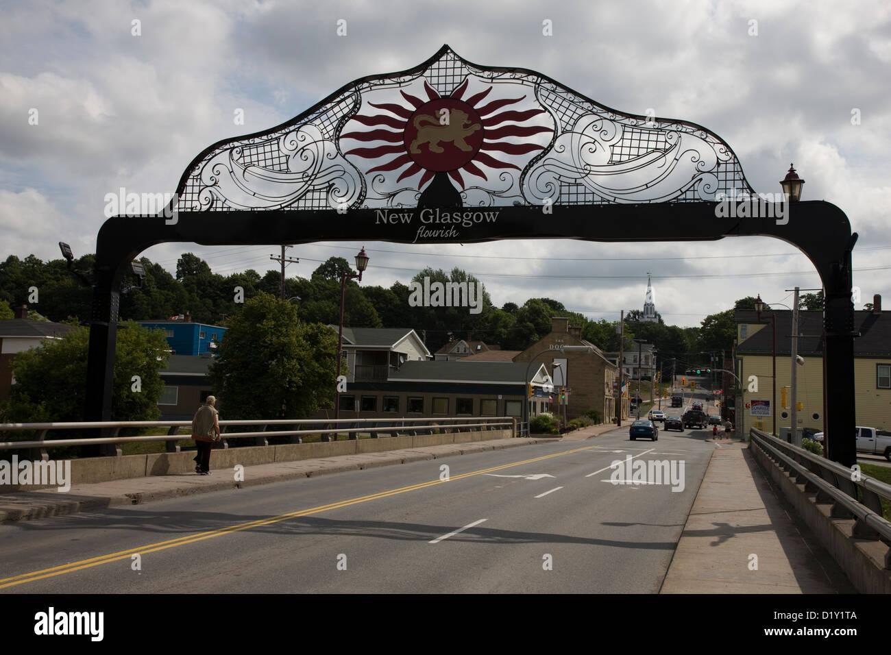"""Strada principale sul fiume in New Glasgow, Nova Scotia, con il gateway e il motto """"fiorire"""" Immagini Stock"""