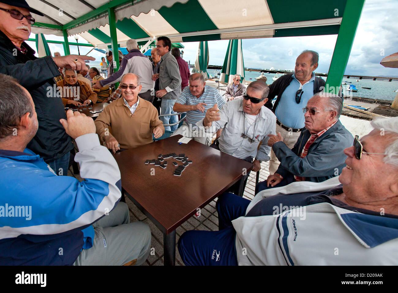 Gli uomini anziani gioca domino in serata, Arrecife, Lanzarote, Isole Canarie, Spagna, Europa Immagini Stock