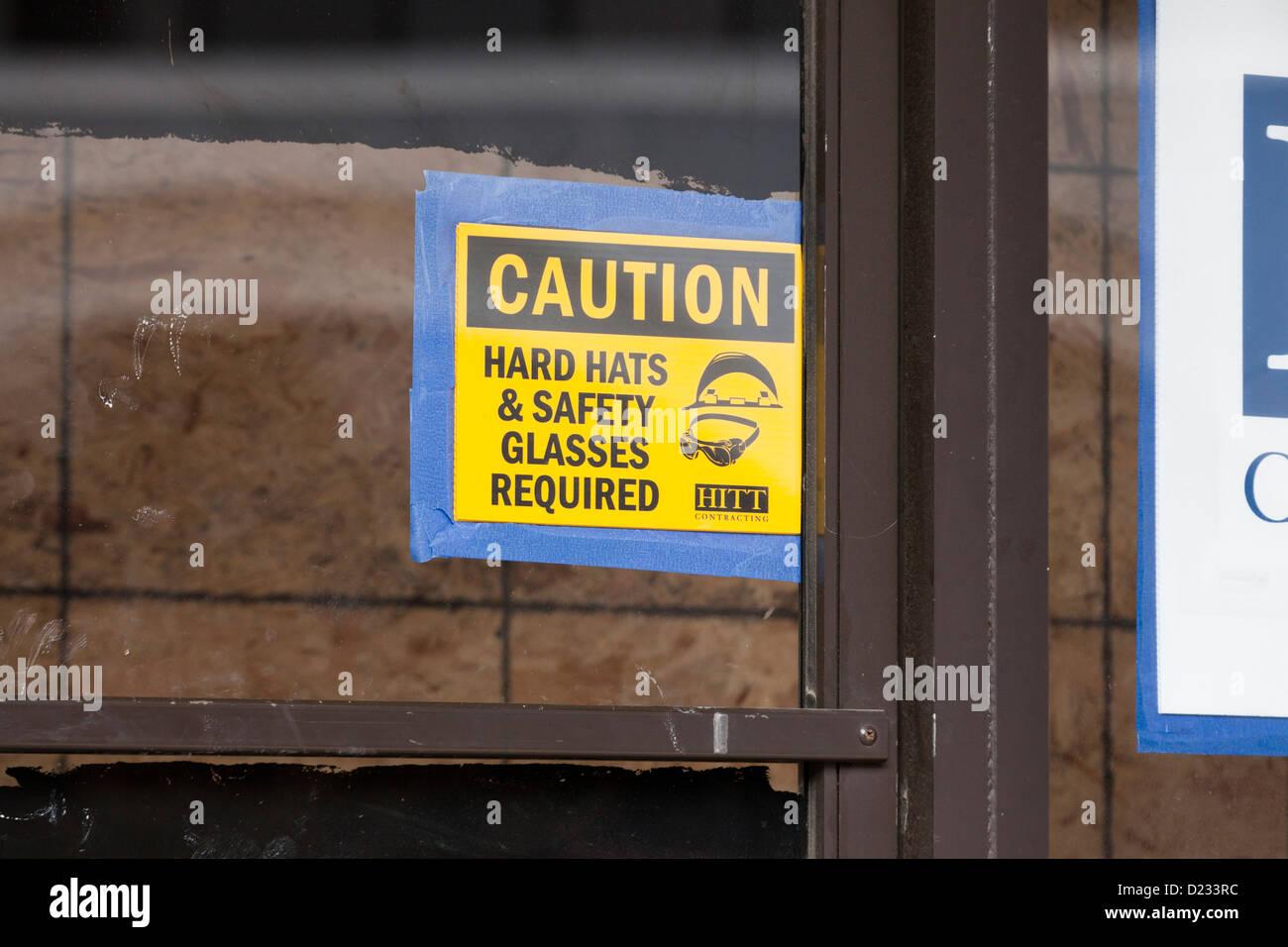 Elmetto e occhiali di sicurezza necessario segno di attenzione Immagini Stock