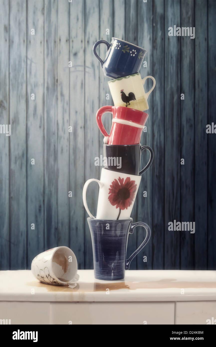 Una pila di tazze equilibrato, una tazza di caffè versato Immagini Stock