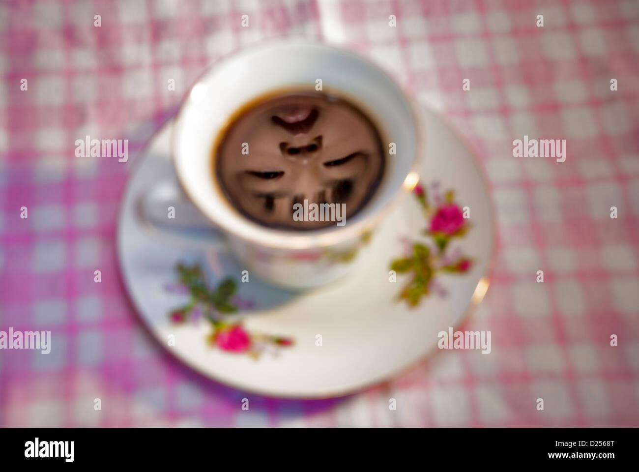 Tazza di caffè nero con la riflessione di un volto umano Immagini Stock