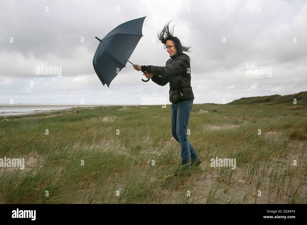Sankt Peter-Ording, Germania, una donna è camminare nel vento e pioggia sulla spiaggia Immagini Stock
