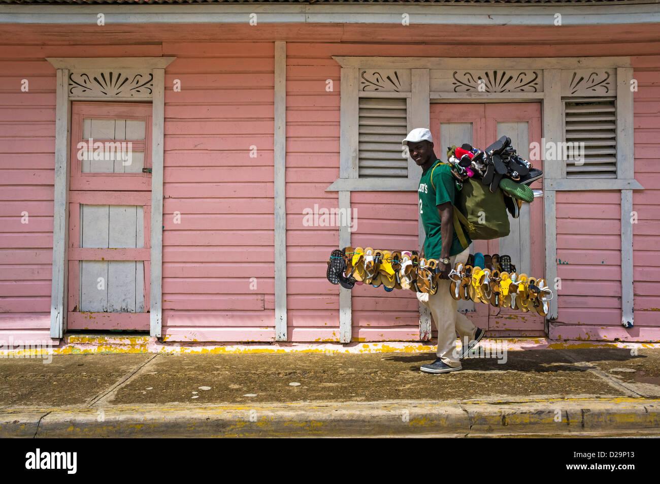 Uomo scarpe vendita passeggiate passato poco case rosa in Otra Banda, La Altagracia provincia, Repubblica Dominicana Immagini Stock
