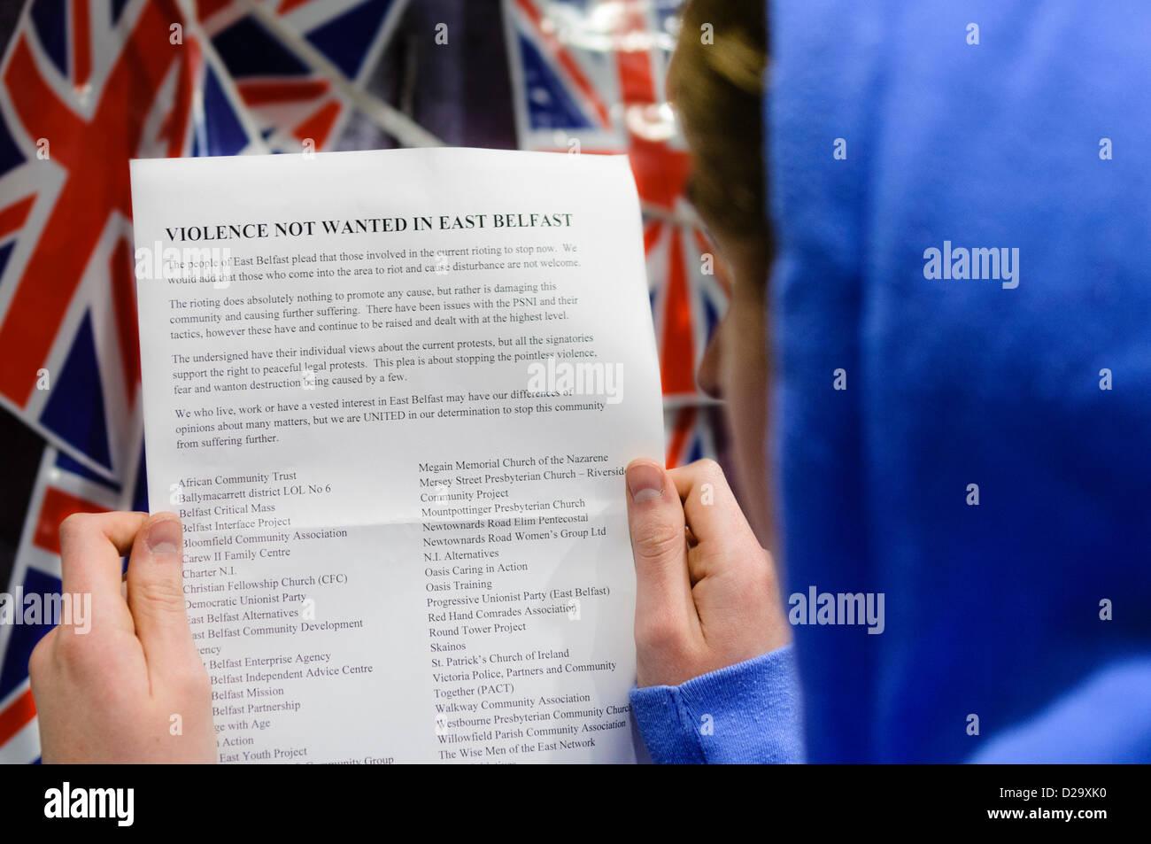 Belfast, Regno Unito. Il 17 gennaio 2013. Una gioventù legge una delle migliaia di volantini che circolano Immagini Stock