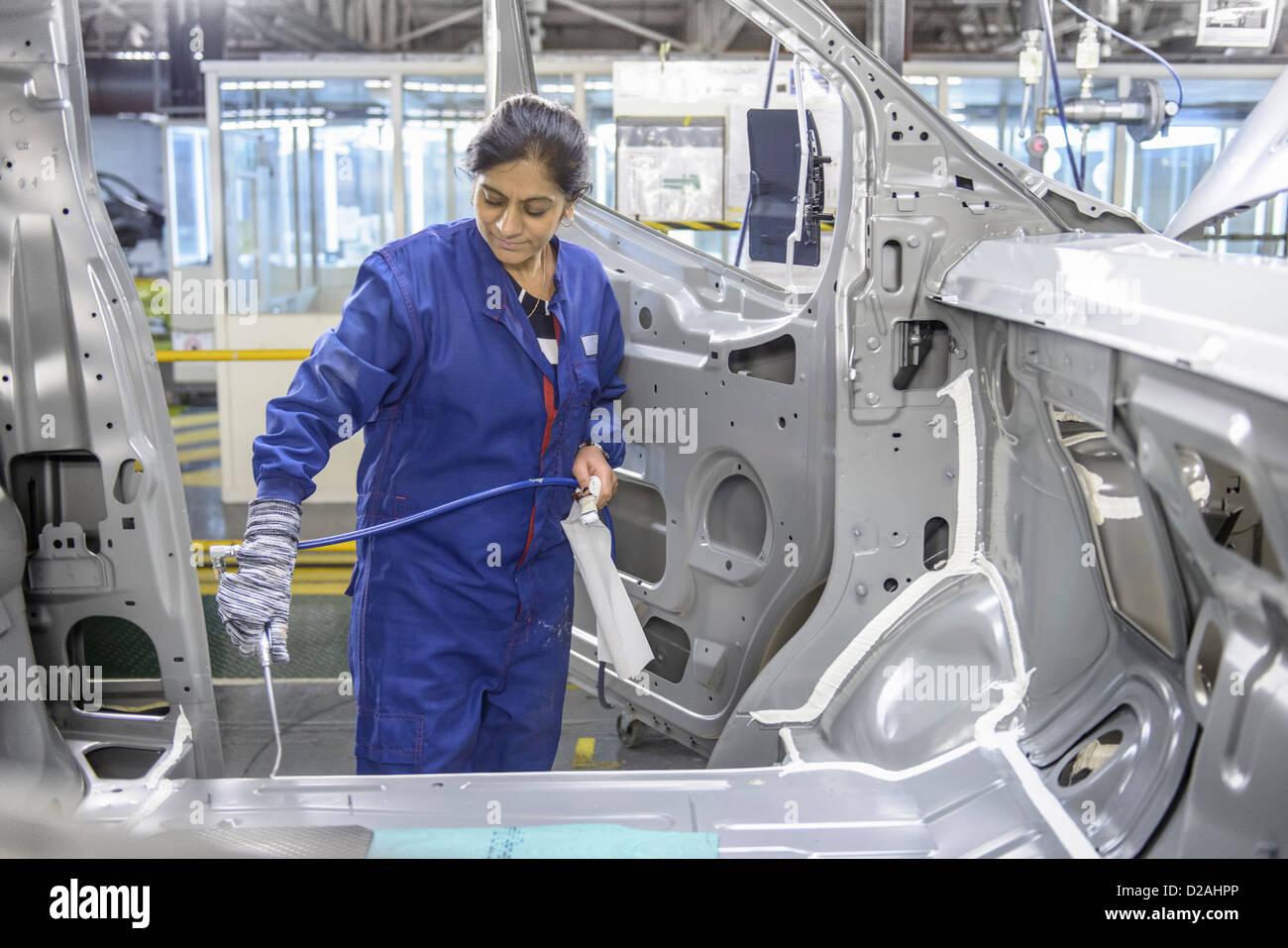 Lavoratore l'applicazione di sigillante nella fabbrica di automobili Immagini Stock