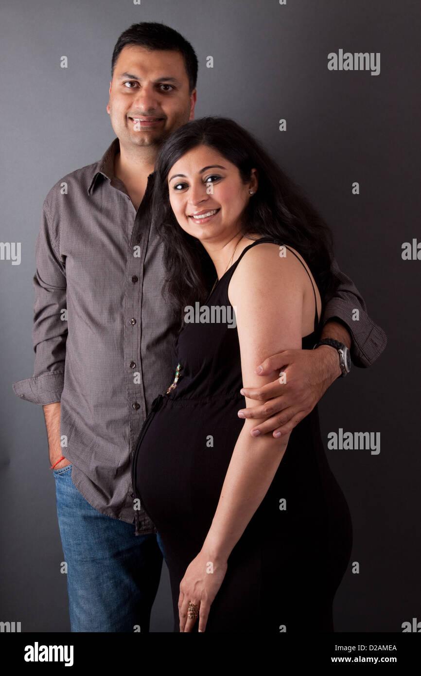 Un East Indian uomo abbraccia la sua moglie incinta Immagini Stock