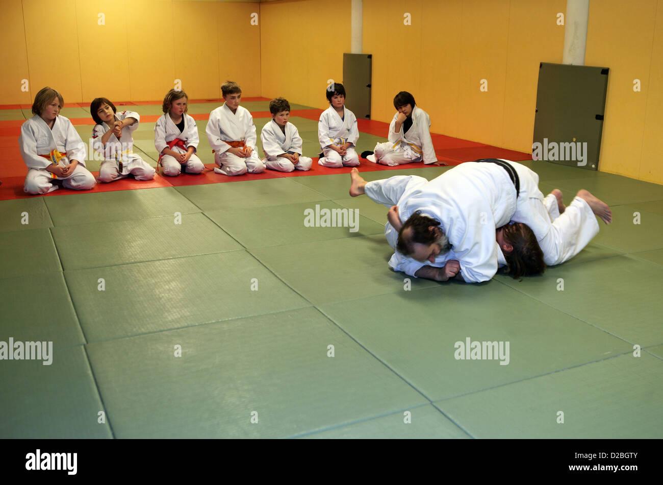 Berlino, Germania, i bambini in un corso di judo. Il judo istruttore illustra una tecnica di proiezione Immagini Stock