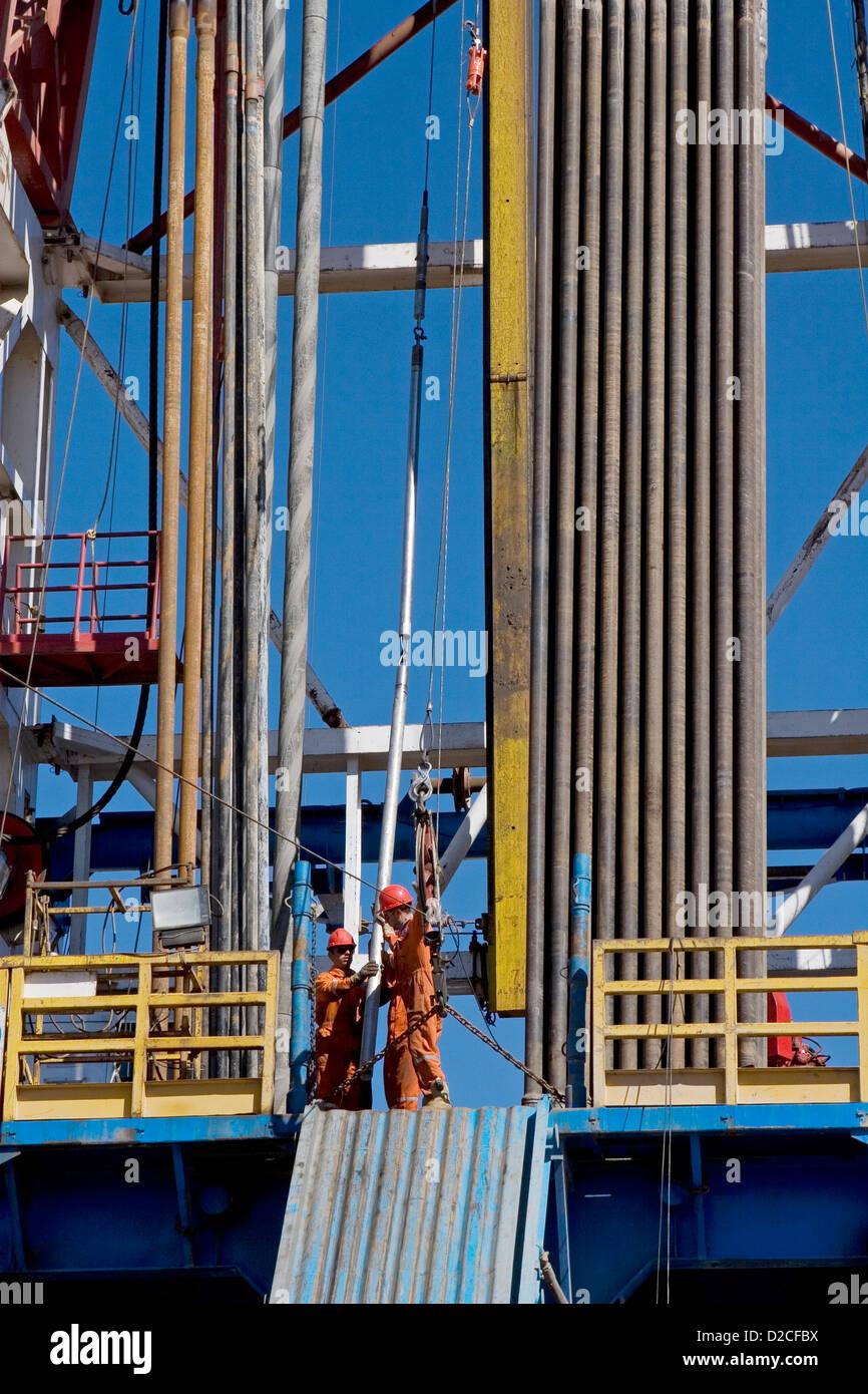 Onshore di esplorazione di petrolio e gas sito. Filo strumenti linea essendo sollevata fino alla piattaforma di Immagini Stock