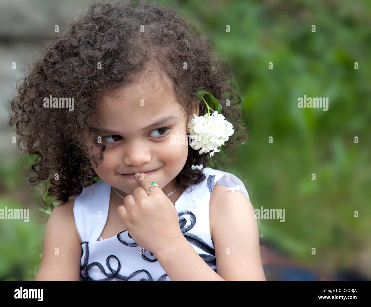 Un giovane multi etnico bambino è timido e timida di espressione Immagini Stock