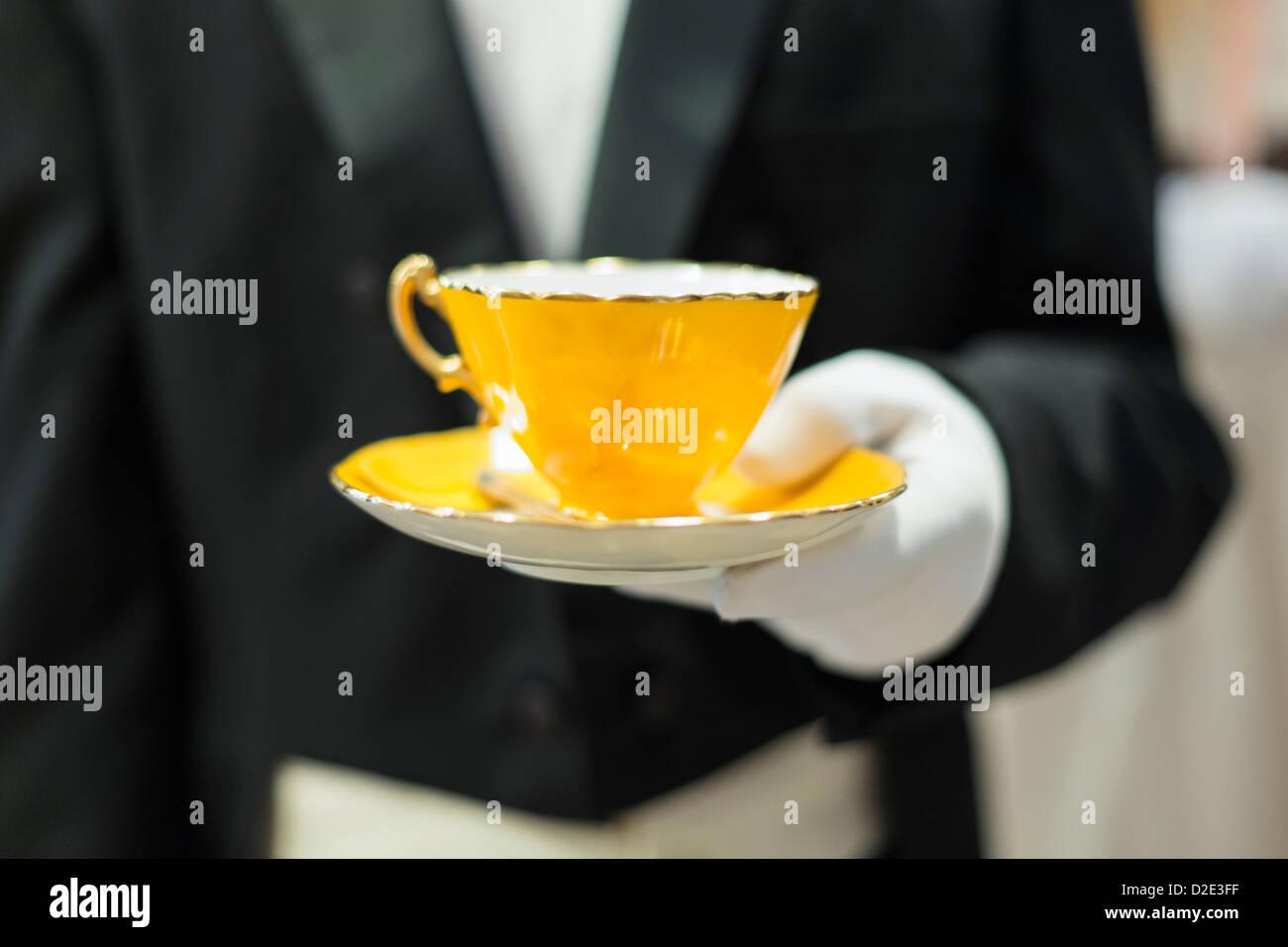 Il gloved bianco mano che tiene un giallo tazza da caffè con piattino Immagini Stock