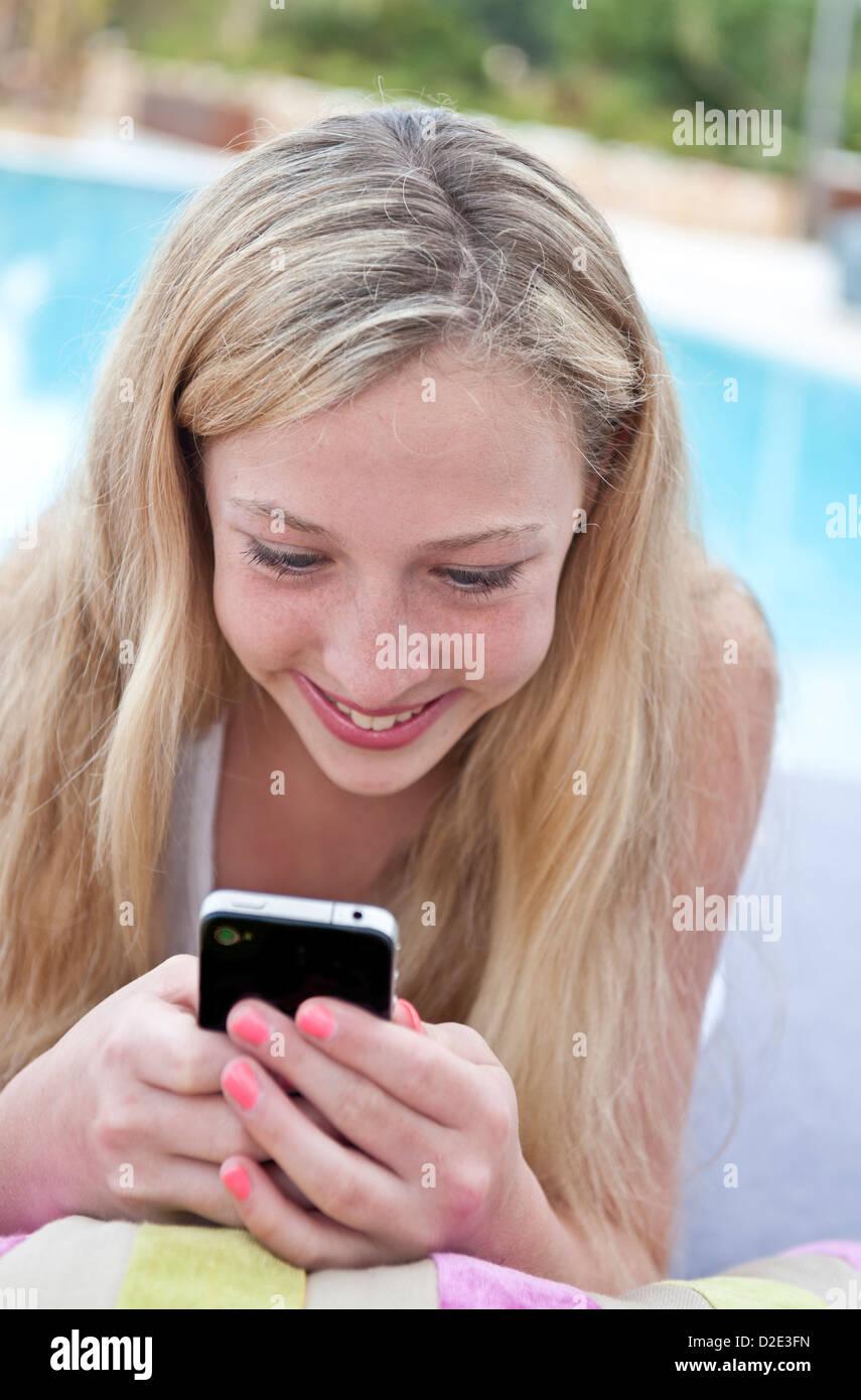 Ragazza adolescente & Smartphone iPhone in vacanza piscina (NB utilizzazioni positive non solo sexting etc) Immagini Stock