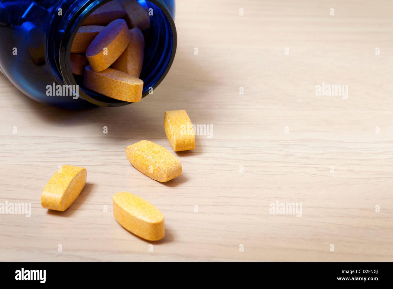 Bottiglia blu di giallo vitamina pillole con alcuni fuoriuscita sul tavolo Immagini Stock