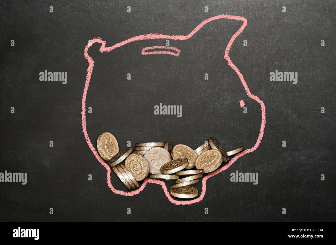 Denaro (Sterling) monete in un salvadanaio disegnati su una lavagna Immagini Stock
