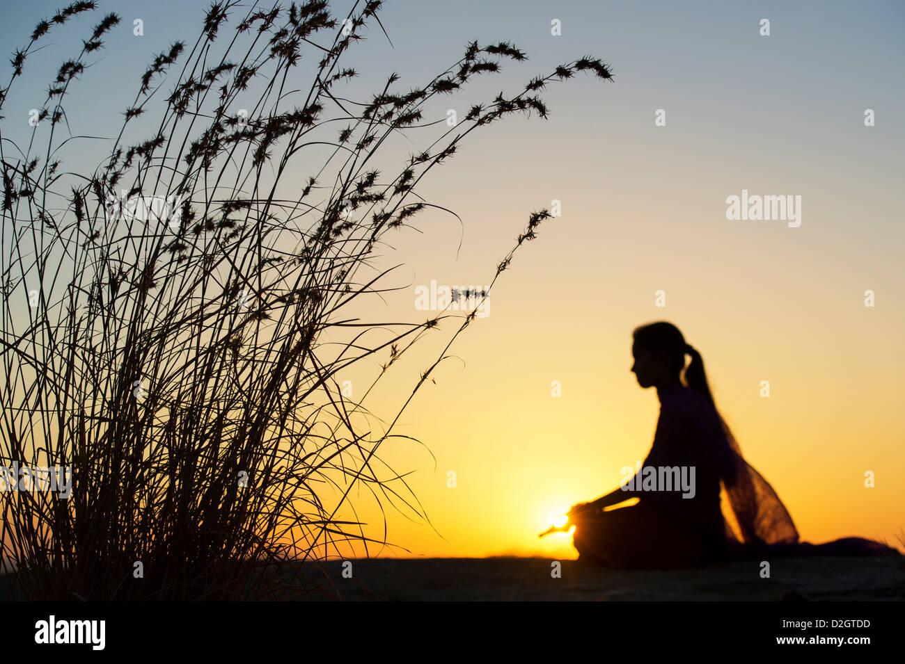 Sunset silhouette di una ragazza indiana meditando. Andhra Pradesh, India Immagini Stock
