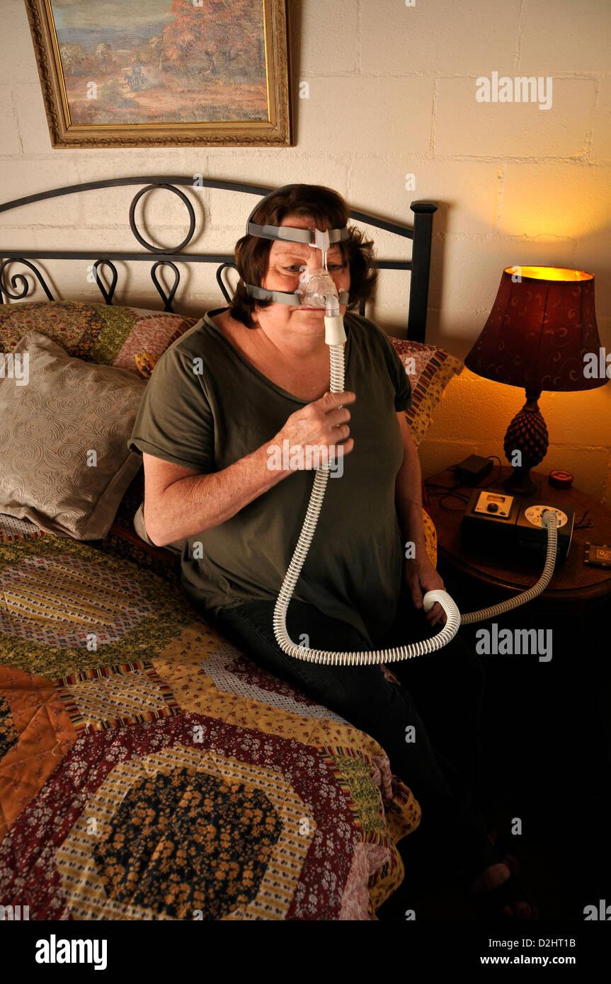 A malati cronici paziente applica un bi-pap macchina che distribuisce aria in continuo durante il sonno per il trattamento Immagini Stock