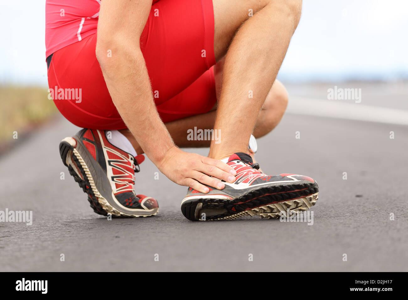 Sezione bassa del giovane maschio runner toccando il piede nel dolore a causa della caviglia slogata su strada Immagini Stock