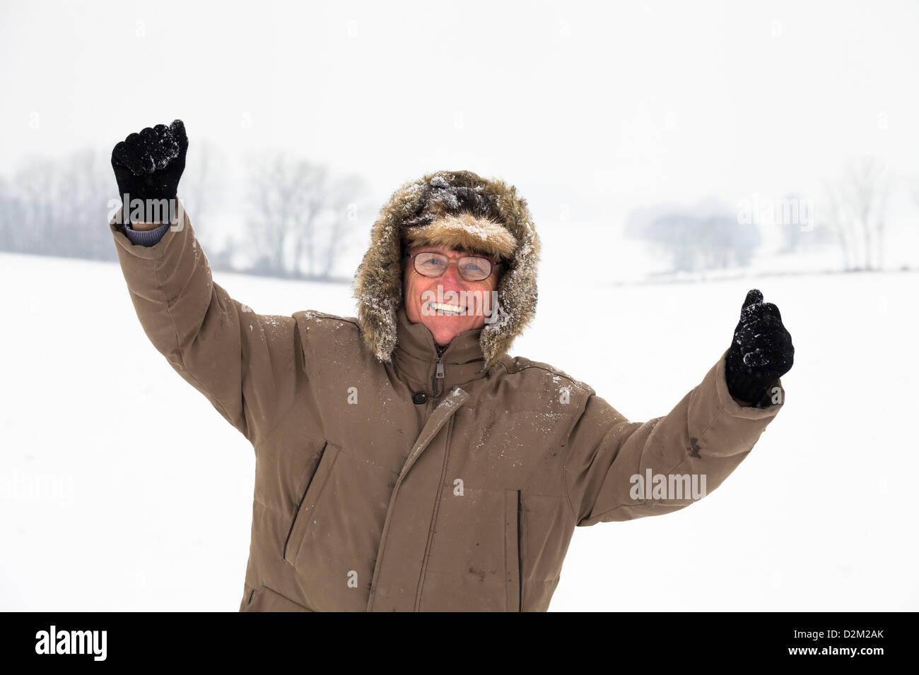 Felice estatica uomo senior godendo di neve in inverno e all'aperto. Immagini Stock