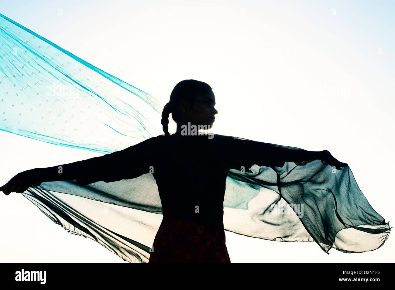Ragazza indiana con veli di sterzata nel vento verso il sole. Silhouette. India Immagini Stock