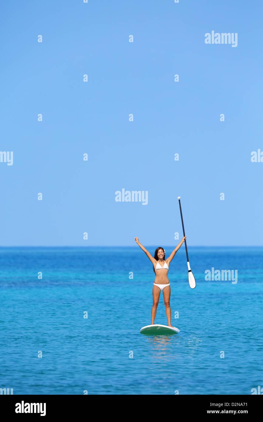 Bellissima gara di misto sulla ragazza paddleboard hawaiano con le braccia sollevate nella felicità godendo Immagini Stock