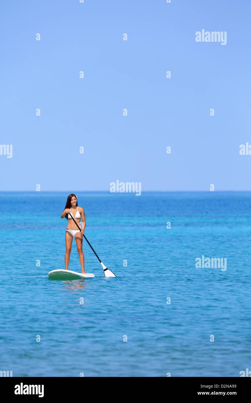 Bella donna multietnica surf su stand up paddleboard sulla Big Island delle Hawaii, Immagini Stock