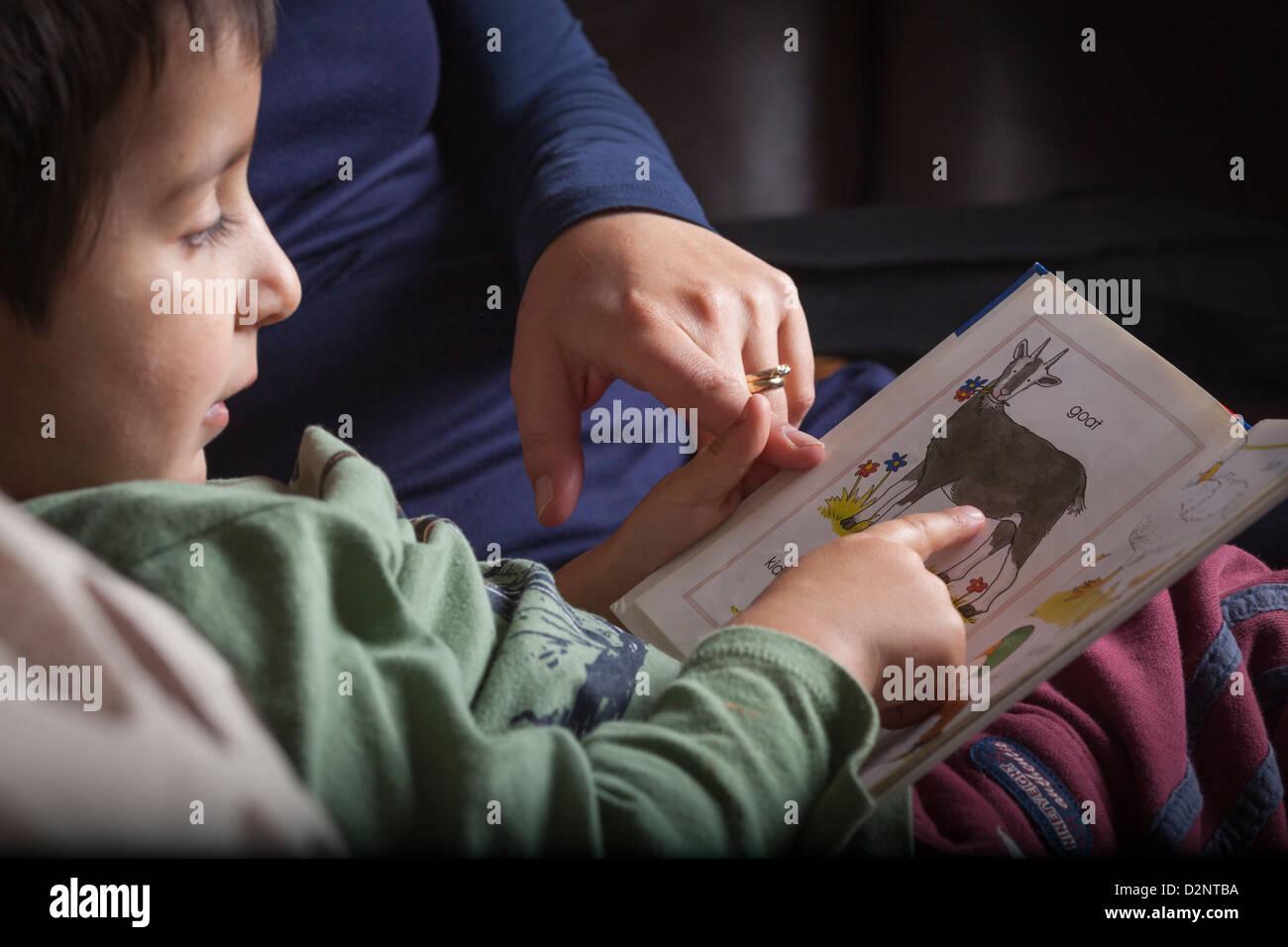 La Madre insegna 4 anni vecchio ragazzo per leggere Foto Stock