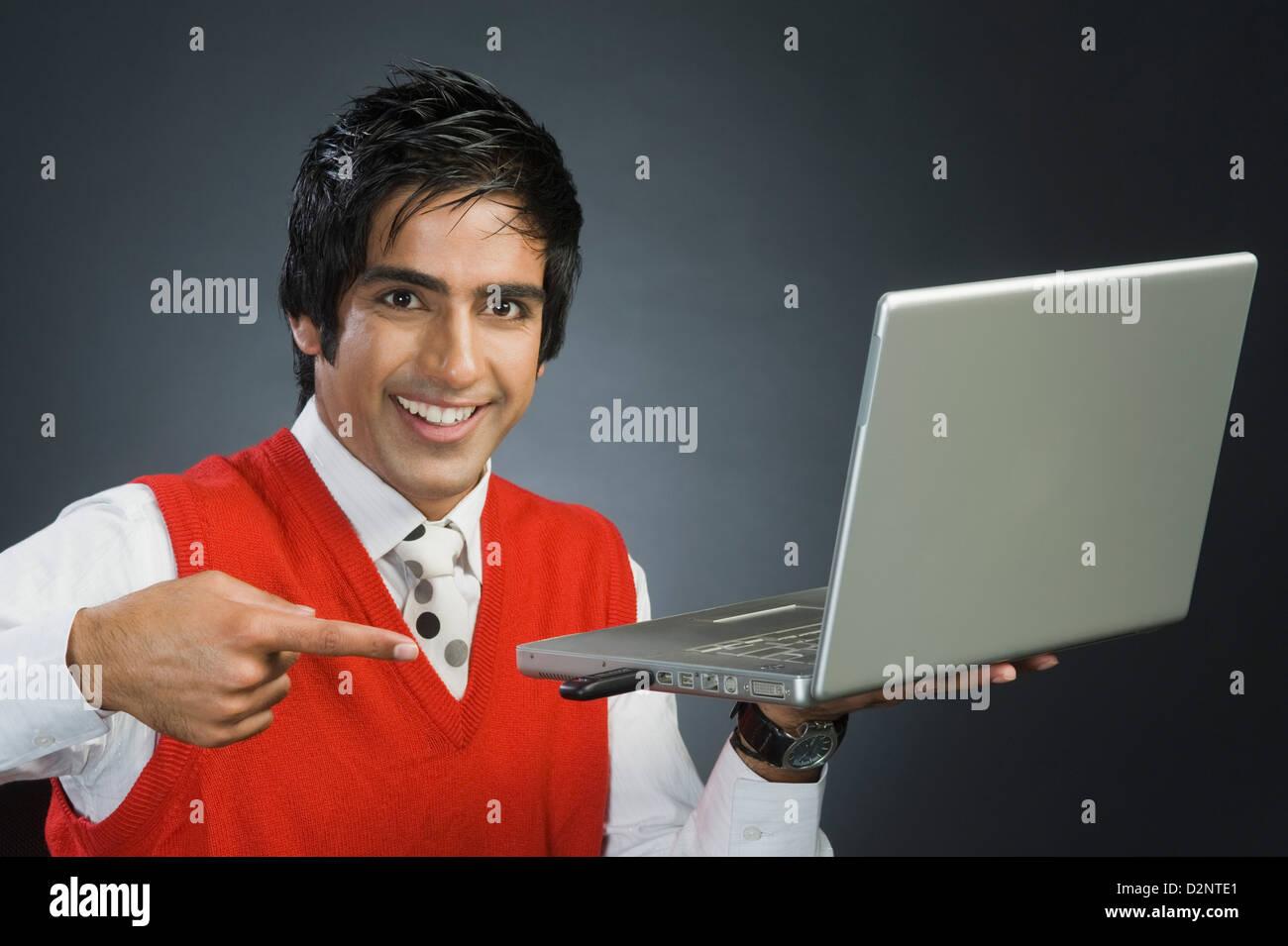 Imprenditore puntando verso un dispositivo USB collegato a un computer portatile Immagini Stock