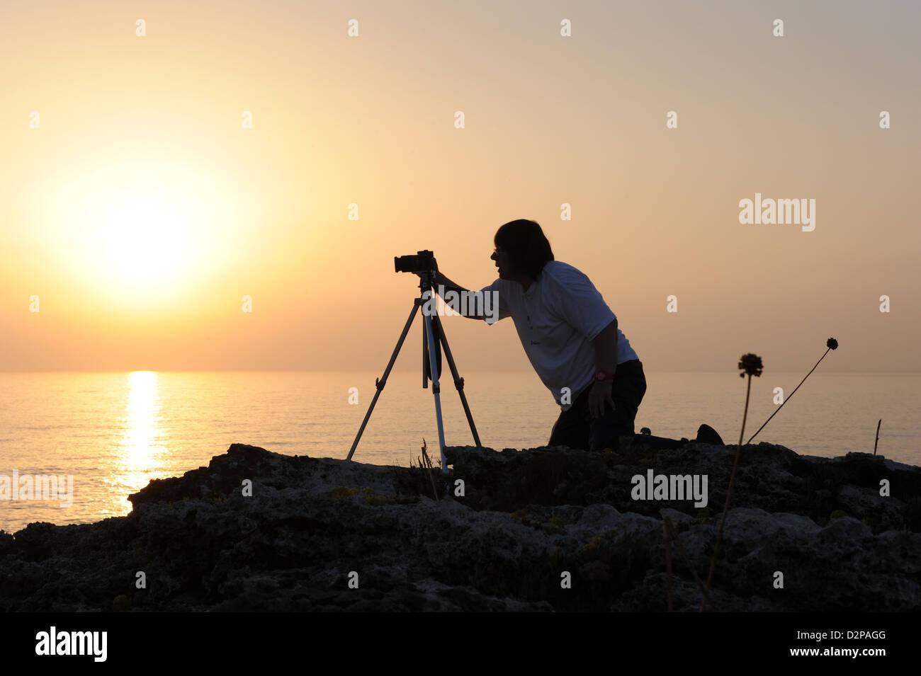 Silhouette di un fotografo di scattare le foto utilizzando un treppiede all'alba sulla costa di Minorca, Isole Immagini Stock