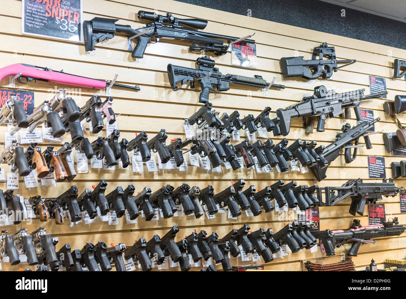Una grande varietà di pistole, fucili e armi in un negozio di pistola. Immagini Stock