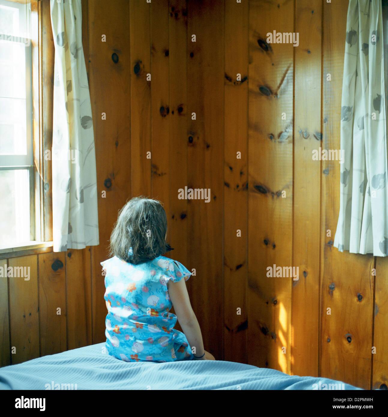Donna seduta sul letto in camera Immagini Stock