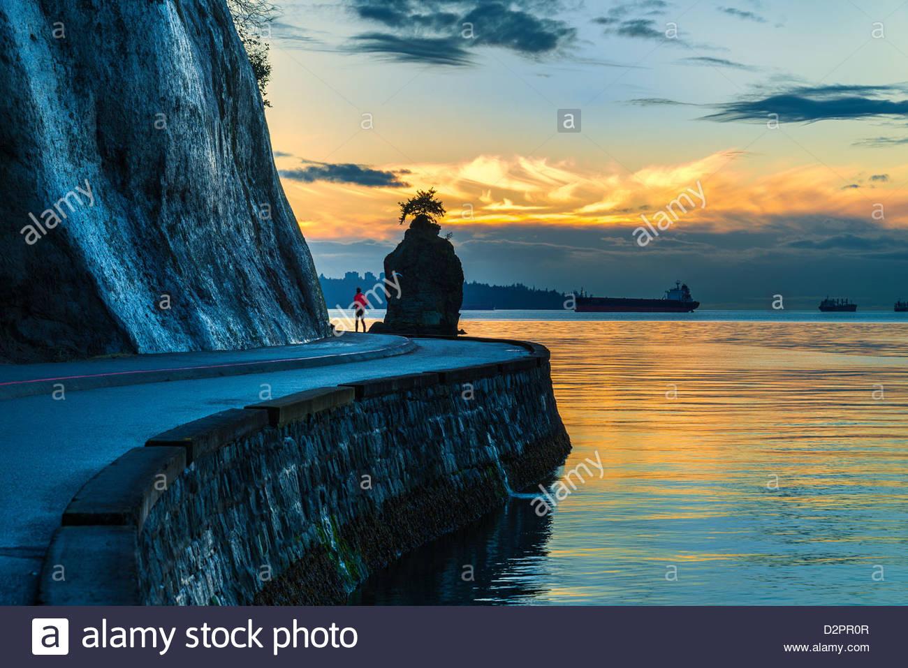 Pareggiatore maschio passa Siwash Rock, su Stanley Park seawall al tramonto, Vancouver, Britsih Columbia, Canada Immagini Stock
