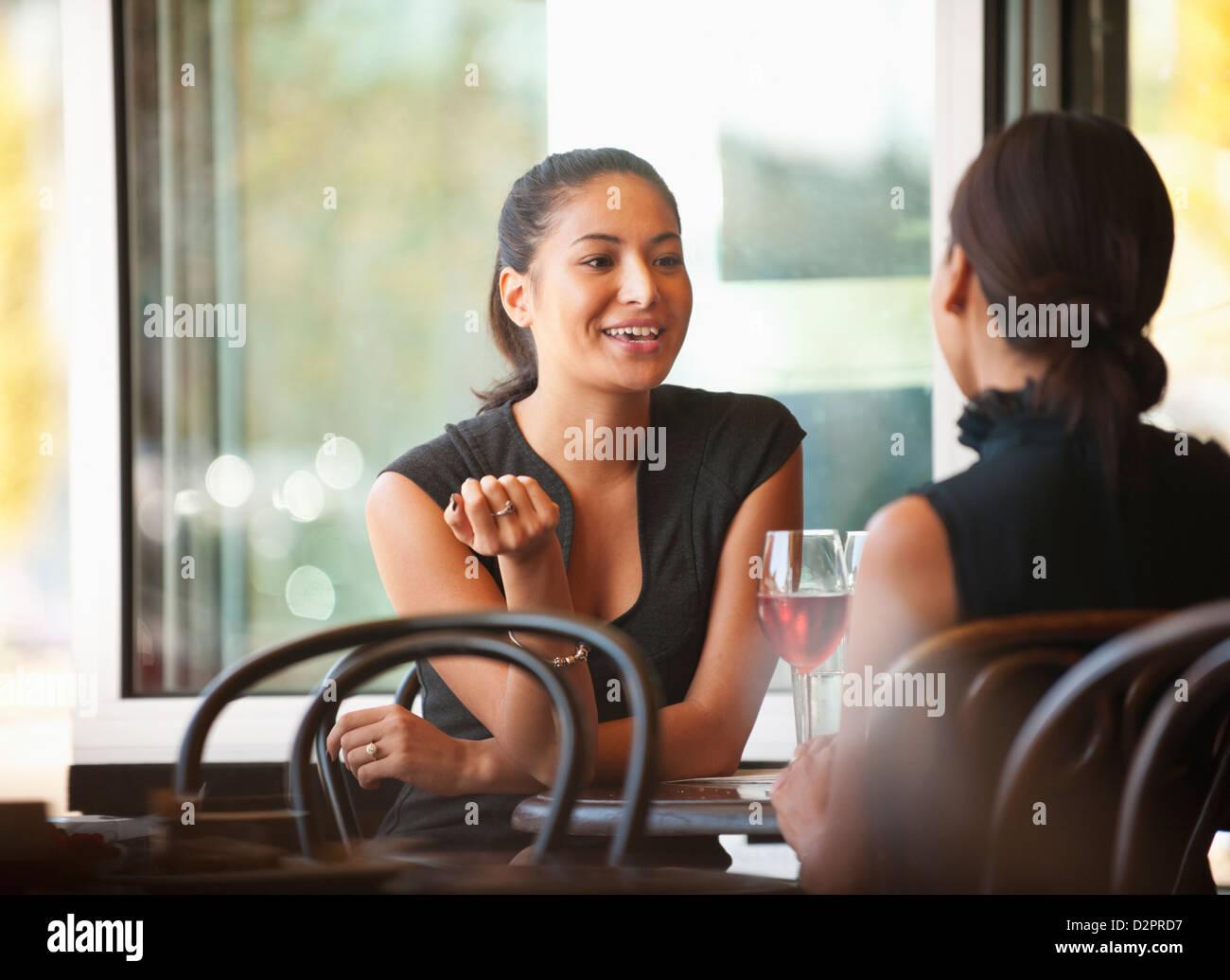 Amici asiatici seduti insieme in cafe Foto Stock