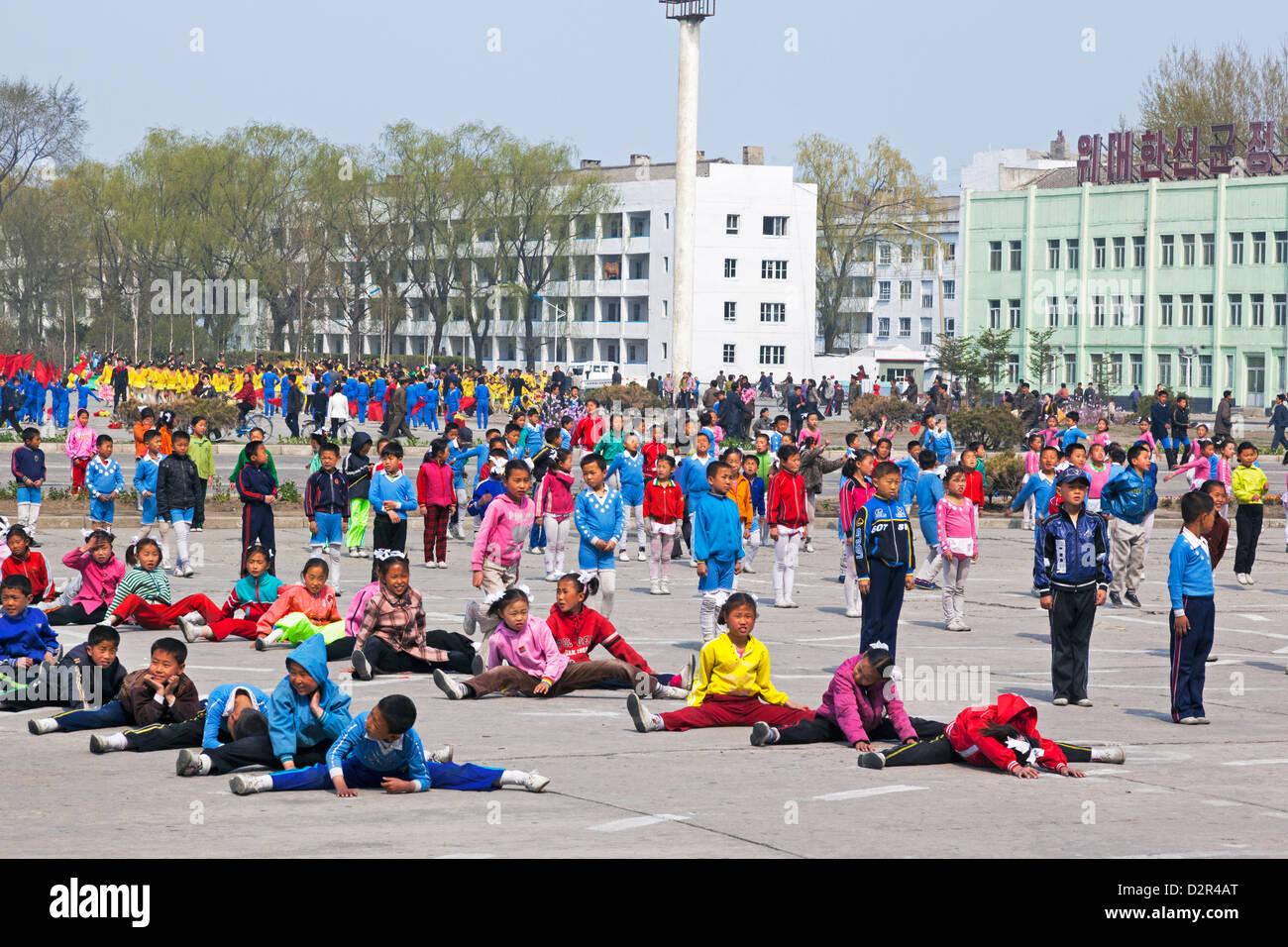 I bambini la pratica dei giochi di massa al di fuori del Grand Theatre, Hamhung, Corea del Nord Immagini Stock