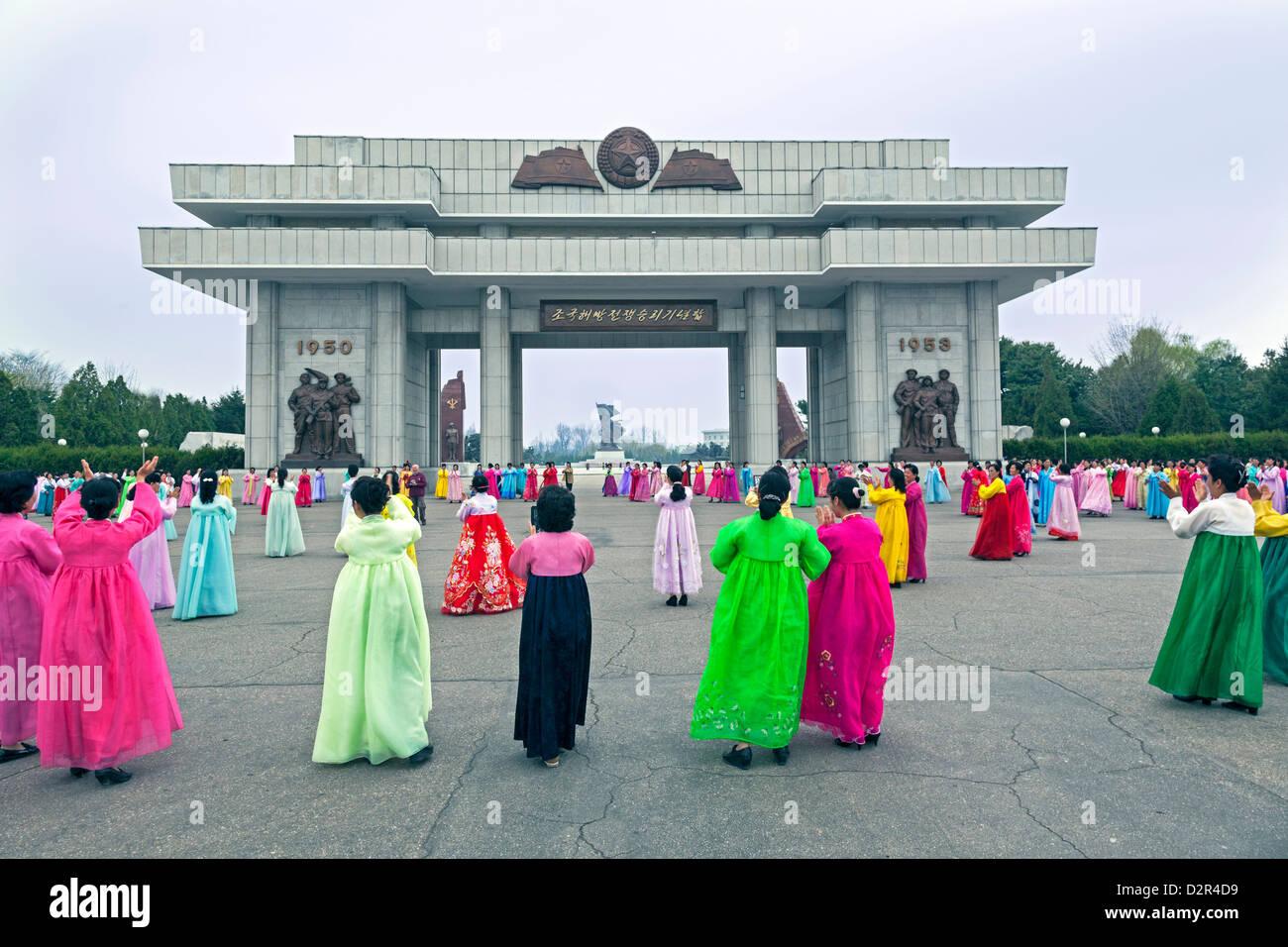 Le donne in variopinti abiti tradizionali a messa a ballare, Pyongyang, Corea del Nord Immagini Stock