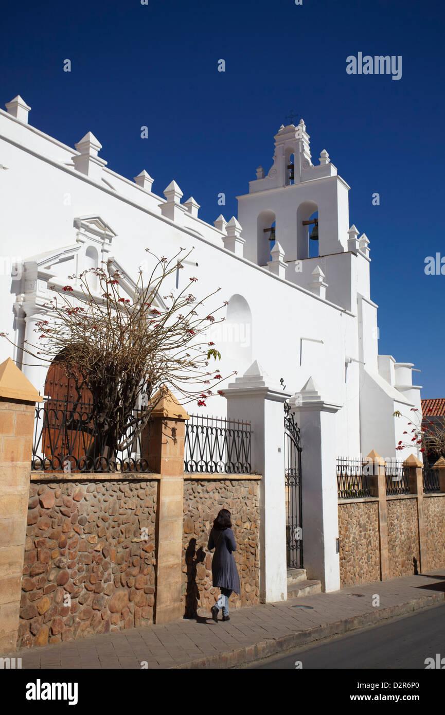 Donna oltrepassando la Iglesia de Santo Domingo, Sucre, Sito Patrimonio Mondiale dell'UNESCO, Bolivia, Sud America Immagini Stock