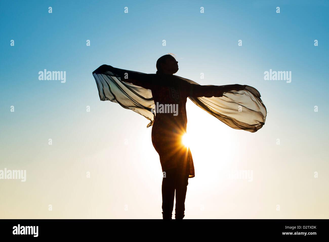 Ragazza indiana con un velo di sterzata nel vento verso il sole. Silhouette. India Immagini Stock