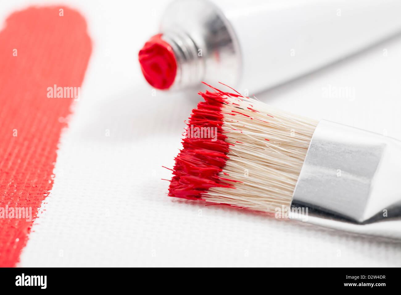 La vernice rossa sulla spazzola di vernice con il tubo di vernice acrilica e corsa di vernice su tela Immagini Stock