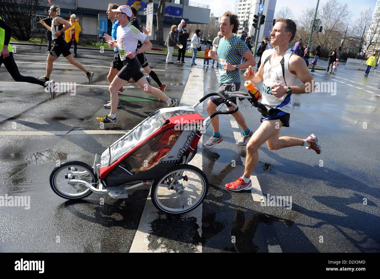 Berlino, Germania, un padre con un bambino carrello al trentesimo Berlino Mezza Maratona Immagini Stock