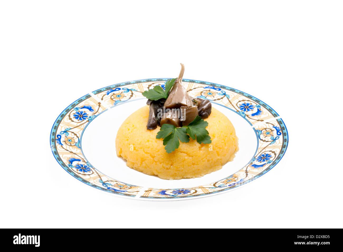 Piastra con polenta di mais e funghi Immagini Stock