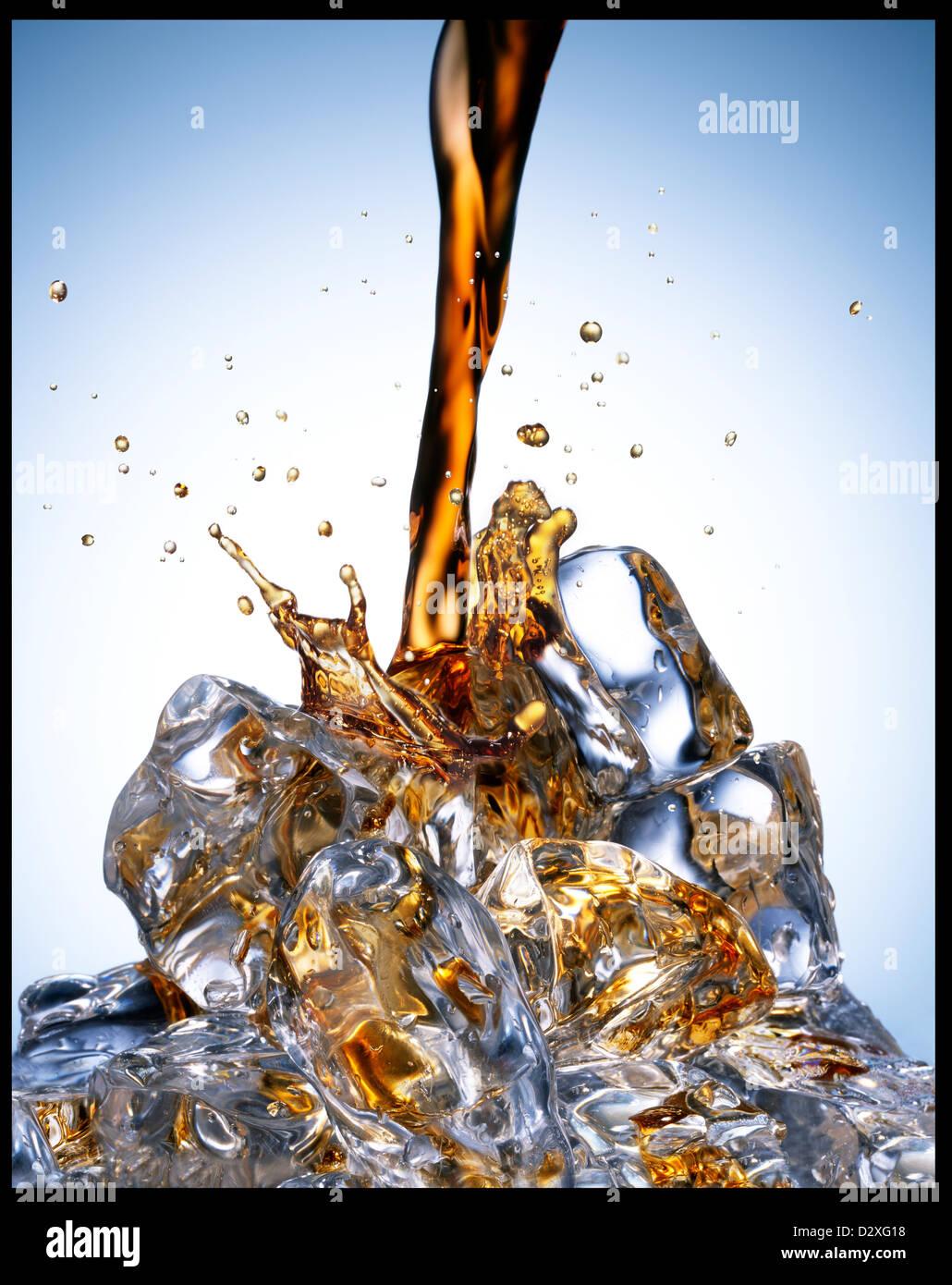Soda versando su ghiaccio Foto Stock