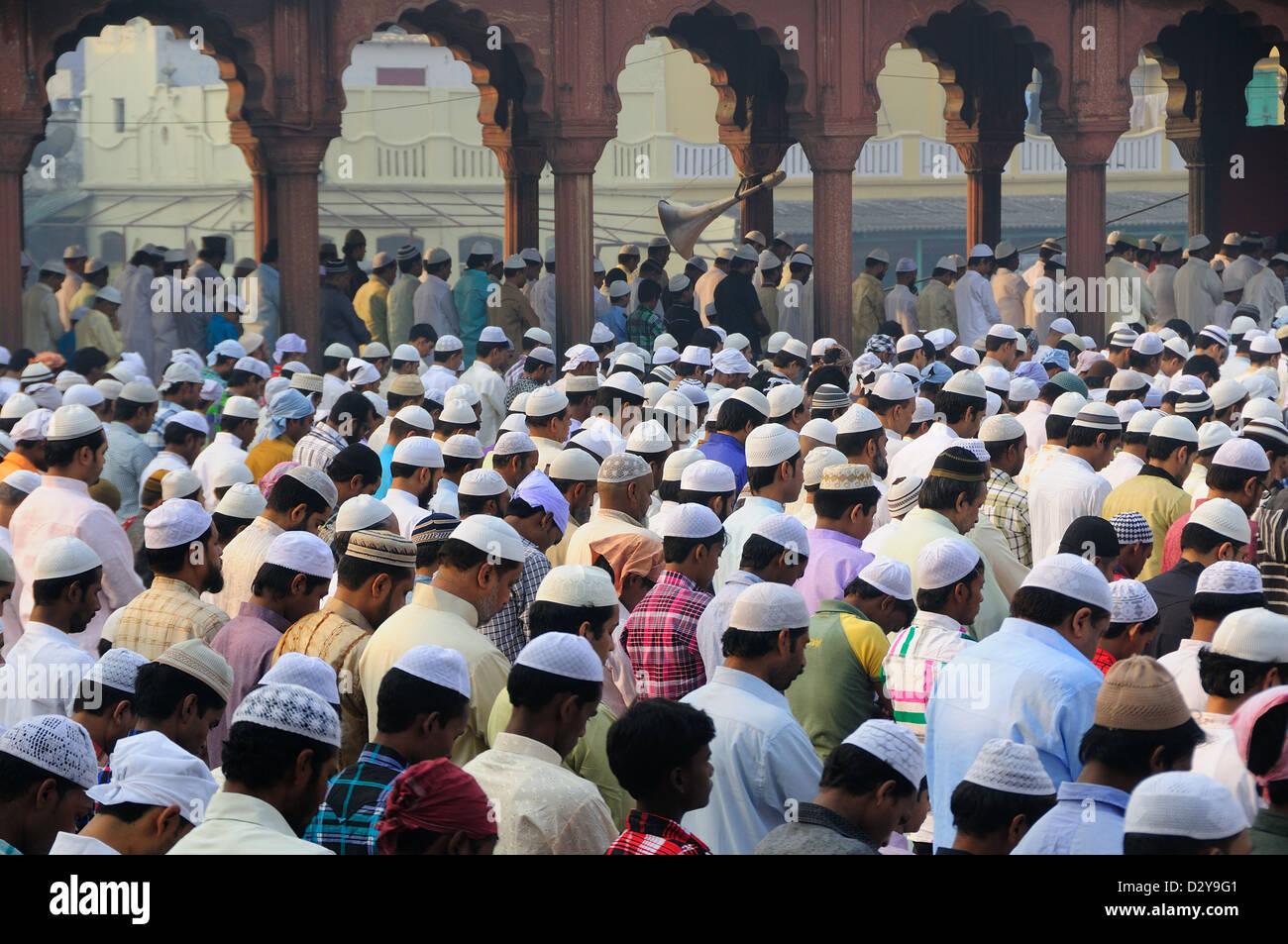 Migliaia di gente musulmana seduta all'interno e al di fuori della moschea. Celebrare la fine del Ramadan. Immagini Stock
