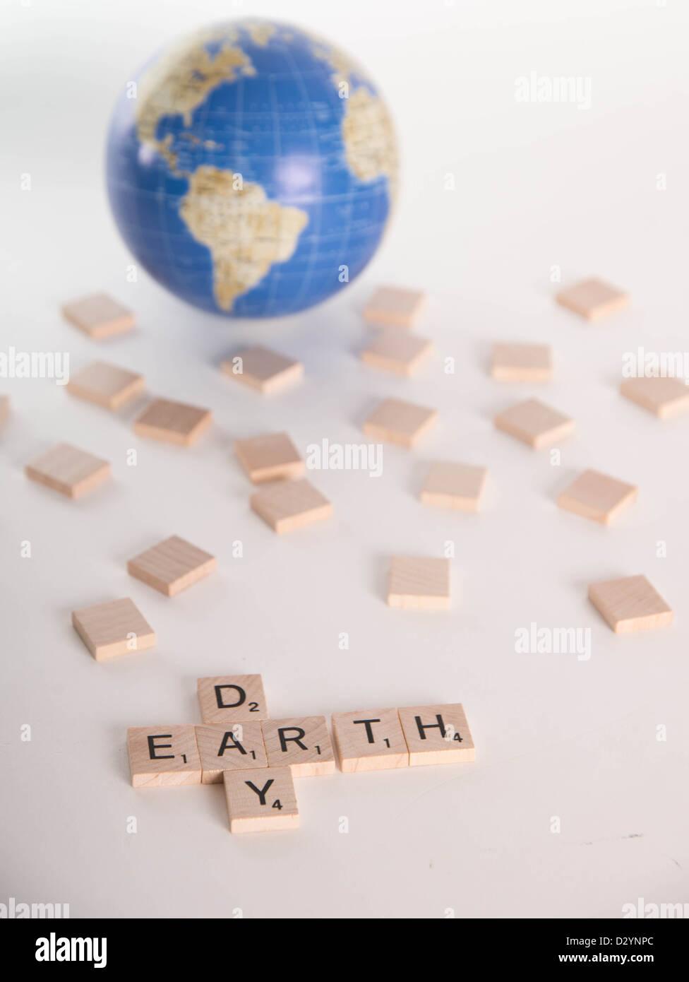 """Concetto: """"La Giornata della Terra' enunciato nelle lettere di Scrabble con fuori fuoco globo in background. Immagini Stock"""
