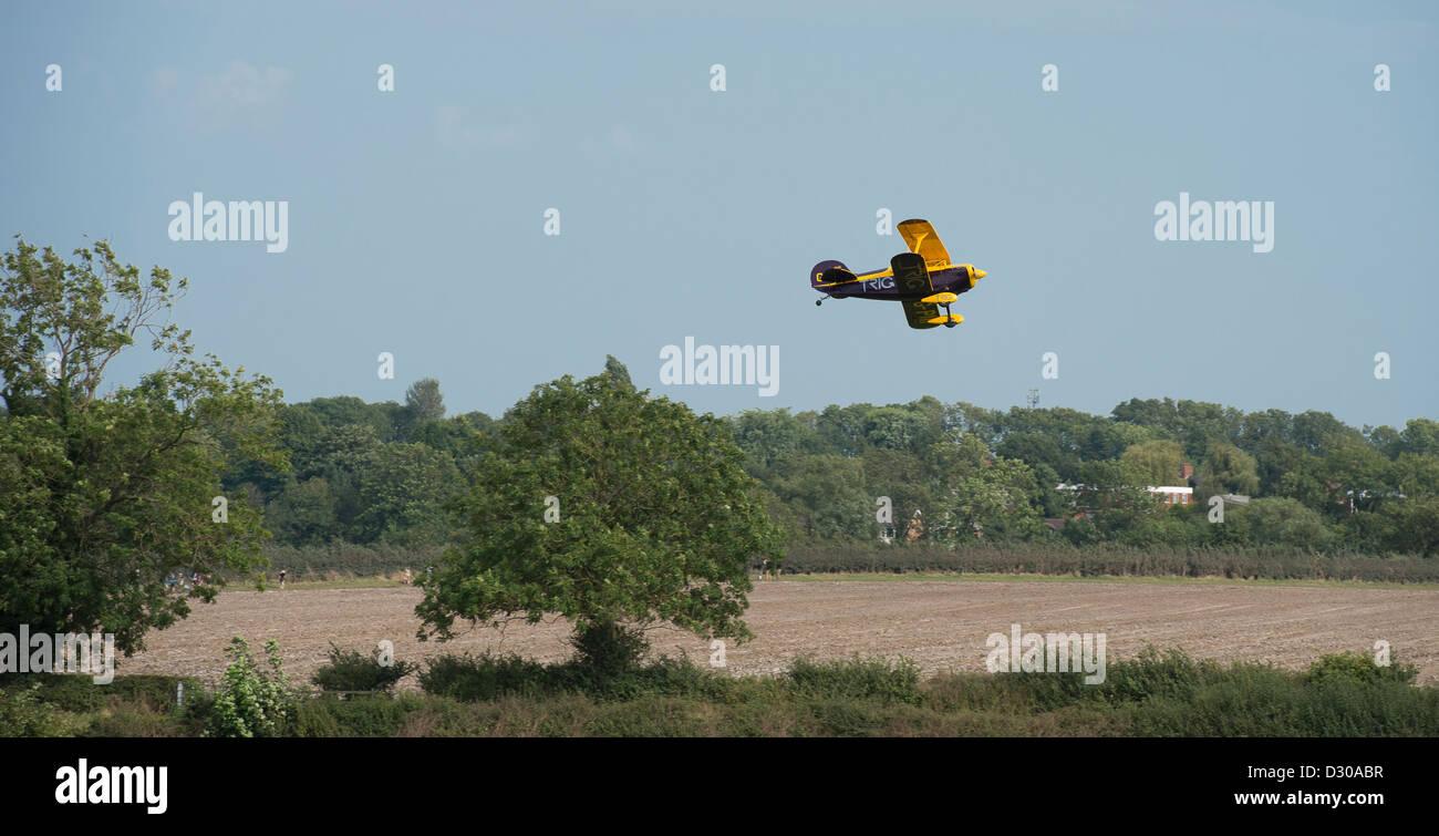 Piccolo biplano volando sopra la splendida campagna inglese. Immagini Stock
