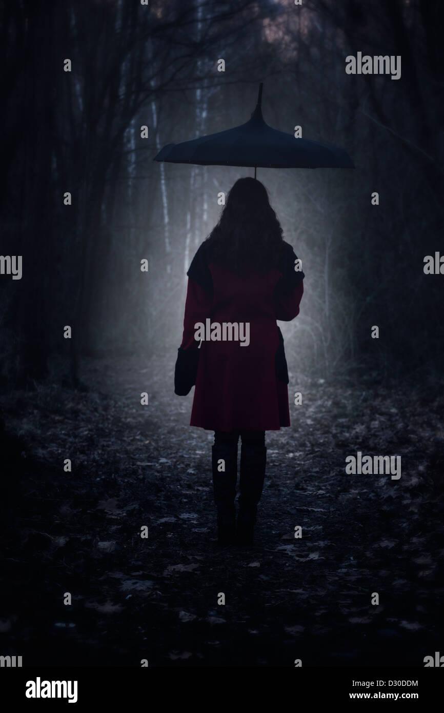 Una donna con un cappotto rosso e un ombrello è a piedi attraverso una foresta scura Immagini Stock