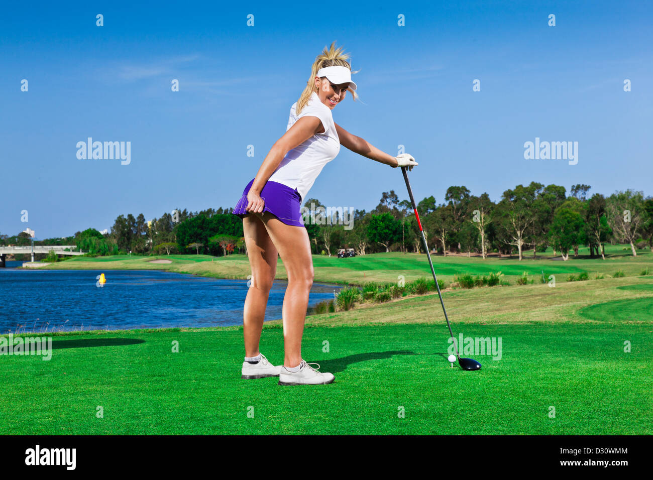 Attraente ragazza di giocatore di golf sul campo da golf con conducente Immagini Stock